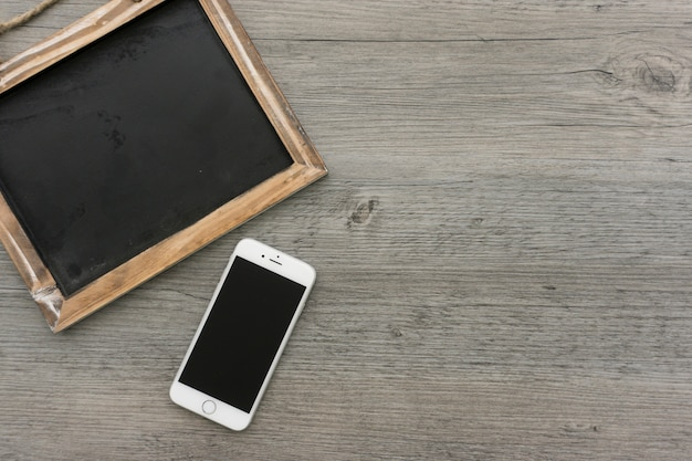 Surface en bois avec le téléphone cellulaire et ardoise vierge