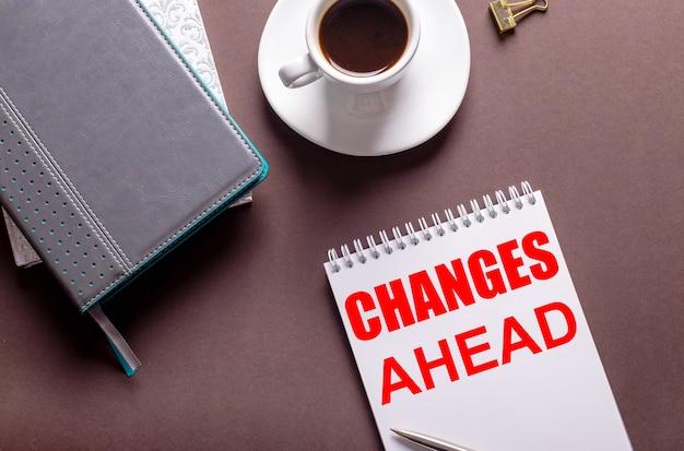 Sur une surface brune, des agendas, une tasse de café blanc et un cahier avec des changements à venir