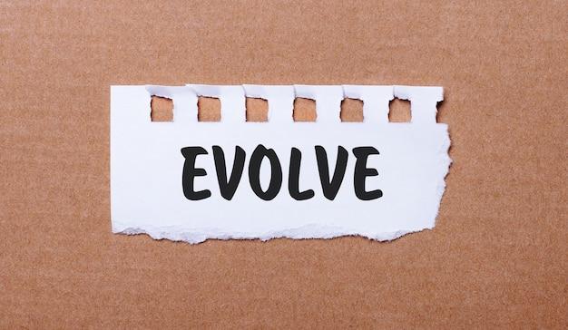 Sur une surface brune, papier blanc avec l'inscription evolve