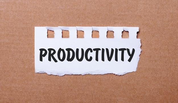 Sur une surface brune, papier blanc avec l'inscription productivité