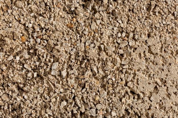 Surface de ciment vieilli avec des roches et des cailloux