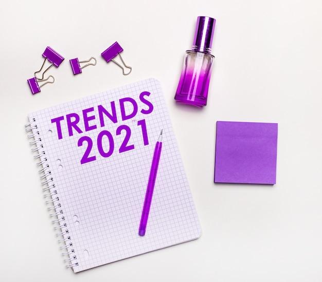 Sur une surface claire - un cadeau lilas, un parfum, des accessoires professionnels lilas et un carnet avec une inscription lilas trends 2021. mise à plat. concept d'entreprise des femmes