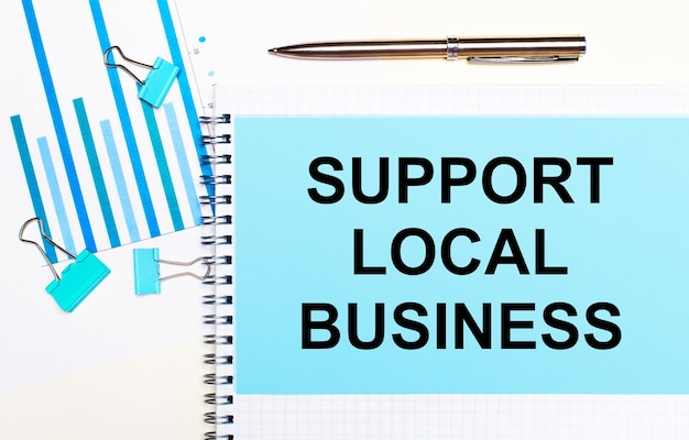 Sur une surface claire, des diagrammes bleu clair, des trombones et une feuille de papier avec le texte soutien des affaires locales. vue d'en-haut. concept d'entreprise