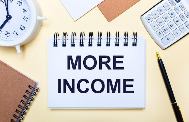 Sur une surface claire, un réveil blanc, une calculatrice, un stylo et un cahier avec le texte plus de revenus