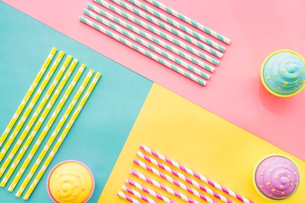 Surface colorée avec des cupcakes et des pailles d'anniversaire