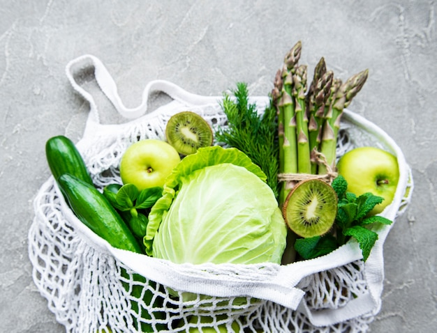 Surface de concept de nourriture végétarienne saine, sélection d'aliments verts frais pour régime de désintoxication, pomme, concombre, asperges, avocat, citron vert, salade dans un sac en filet, vue de dessus sur une surface en béton