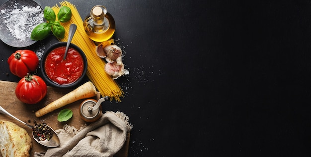 Surface de la cuisine italienne avec des légumes spaghetti et sauce tomate sur une surface sombre