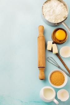 Surface de cuisson avec des ingrédients farine, œufs, sucre, beurre, cannelle, étoile d'anis et ustensiles de cuisine sur table rustique bleu. mise au point sélective. vue de dessus.
