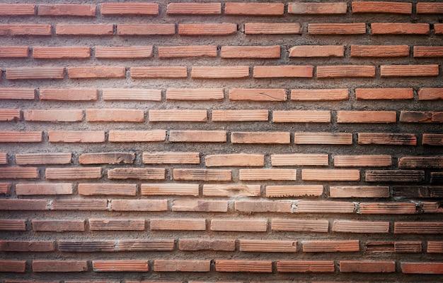 Surface du mur de briques rouges. fond de pierre
