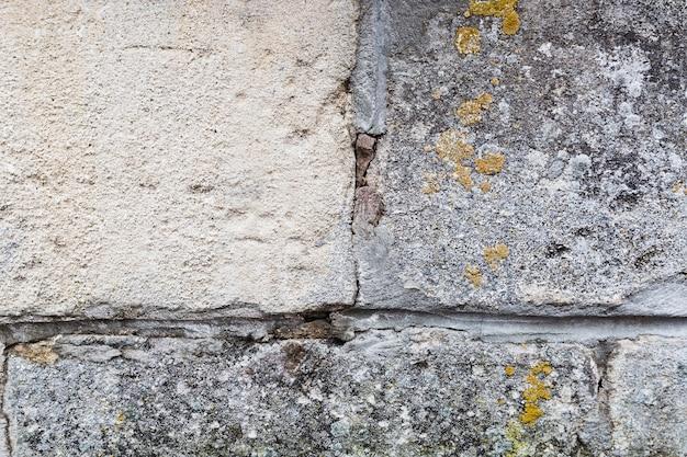 Surface du mur avec des pierres et de la mousse
