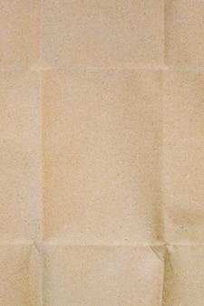 La surface du papier kraft d'emballage beige avec des lignes froissées et des ombres.