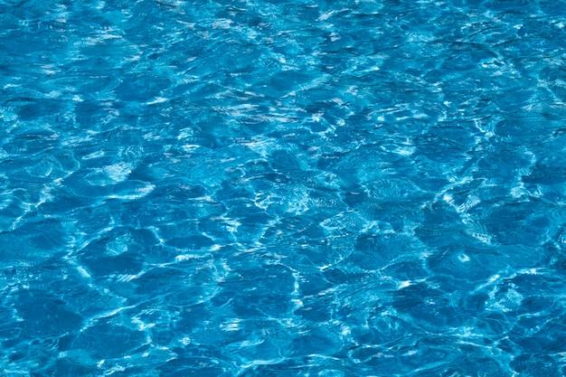 Surface de l'eau bleue et lumineuse de la piscine avec reflet du soleil.