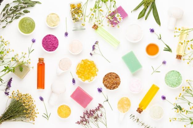 Surface florale d'aromathérapie spa, pose plate de divers produits de soins de beauté décorés de fleurs de camomille simples.