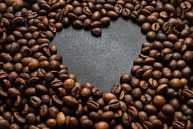 Surface de grains de café torréfiés avec espace en forme de coeur pour le texte sur une surface sombre