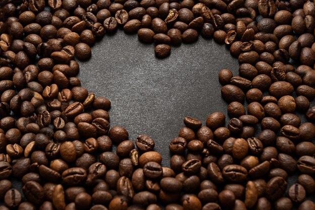 Surface de grains de café torréfiés en forme de coeur sur une surface sombre