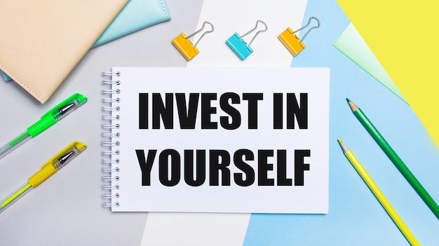 Sur une surface grise et bleue se trouvent des articles de papeterie de couleur jaune-vert, un cahier avec le texte investissez en vous-même
