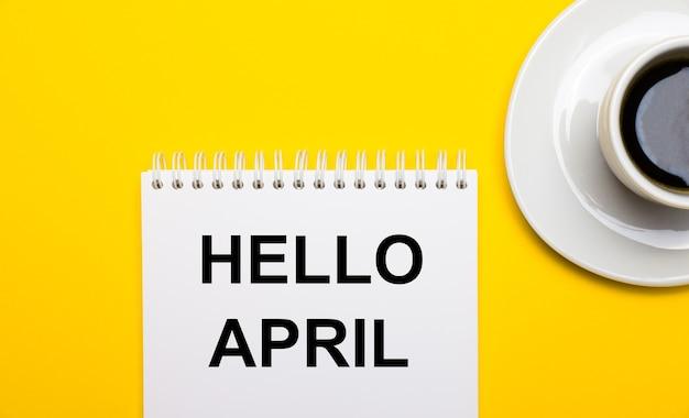 Sur une surface jaune vif, une tasse blanche avec du café et un bloc-notes blanc avec les mots bonjour avril