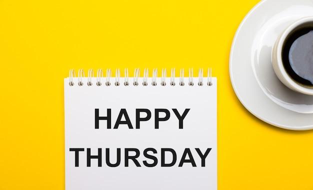 Sur une surface jaune vif, une tasse blanche avec du café et un bloc-notes blanc avec les mots joyeux jeudi