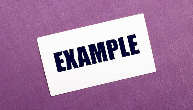 Sur une surface lilas, une carte blanche avec le mot exemple