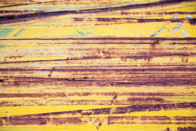 Surface métallique jaune rouillée avec des rayures horizontales en arrière-plan