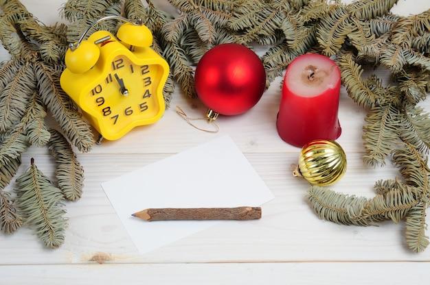 Surface à motifs en bois blanc de noël avec des branches d'arbres de noël, des jouets, une horloge et du papier blanc