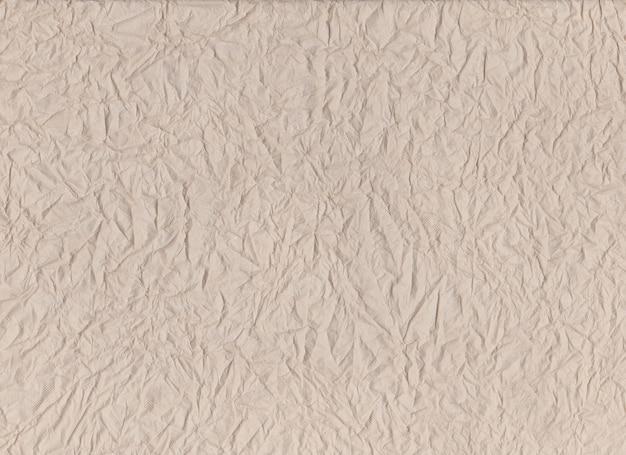Surface d'un mouchoir en papier brun et froissé sur une texture froissée.