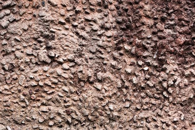 Surface de mur en pierre véritable fissurée, inégale et décorative