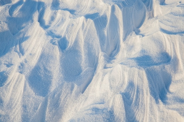 Une surface de neige intéressante et inhabituelle avec de grandes vagues et des saillies éclairées par la lumière du soleil, la structure de la neige en surface