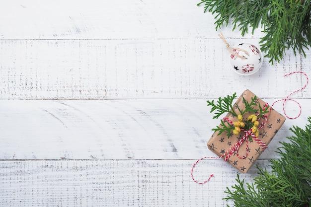 Surface de noël avec des branches de sapin, boîte-cadeau et boule sur table en bois. vue de dessus avec espace de copie.