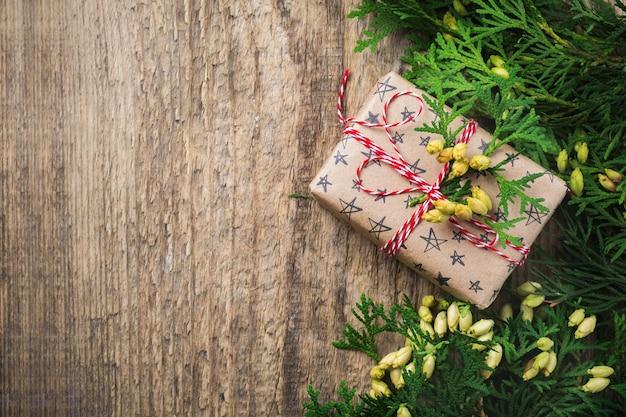 Surface de noël avec des branches de sapin, des jouets, une boîte-cadeau et des cloches sur une table en bois. vue de dessus avec espace de copie.