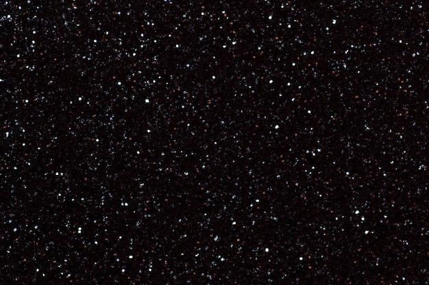 Surface noire brillante floue avec des lumières scintillantes.