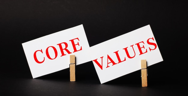 Sur une surface noire sur des pinces à linge en bois, deux cartes vierges blanches avec le texte principales valeurs