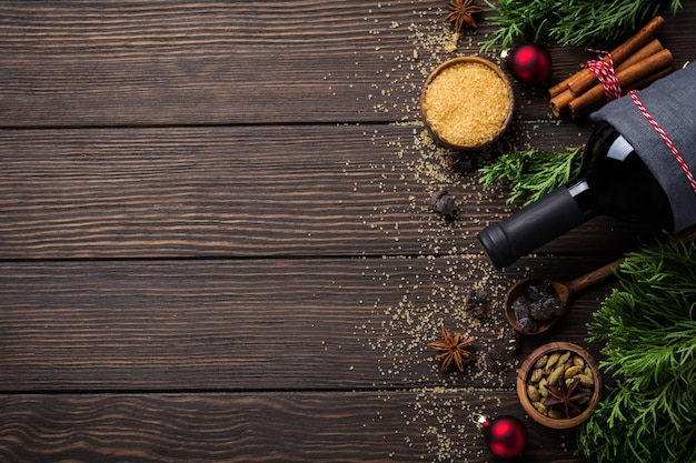 Surface de nourriture de nouvel an. ingrédients pour faire du vin chaud de noël bouteille de vin rouge, orange, sucre de canne et épices.