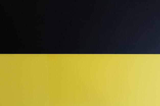 Surface de papier de couleur pastel noir et jaune avec un espace pour le texte