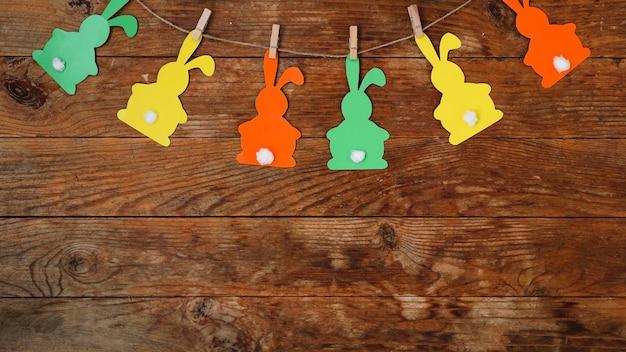 Surface de pâques. guirlande de lapins en papier sur une surface en bois