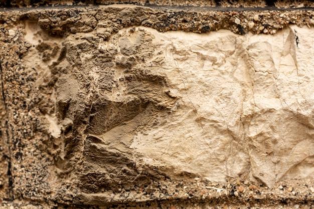 Surface en pierre avec des fissures et une texture rugueuse