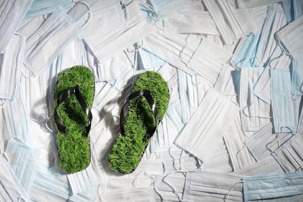 Surface remplie de masques chirurgicaux avec des tongs en herbe verte, à plat
