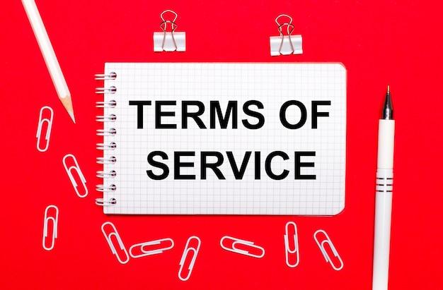 Sur une surface rouge, un stylo blanc, des trombones blancs, un crayon blanc et un cahier avec le texte conditions de service. vue d'en-haut