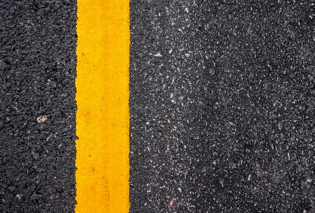 Surface de la route goudronnée avec la ligne jaune
