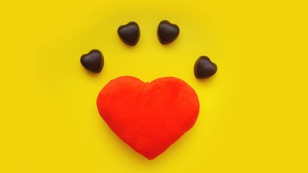 Surface de la saint-valentin avec cœur en peluche et chocolats sur une surface jaune. vue de dessus. pour la bannière, la conception de cartes