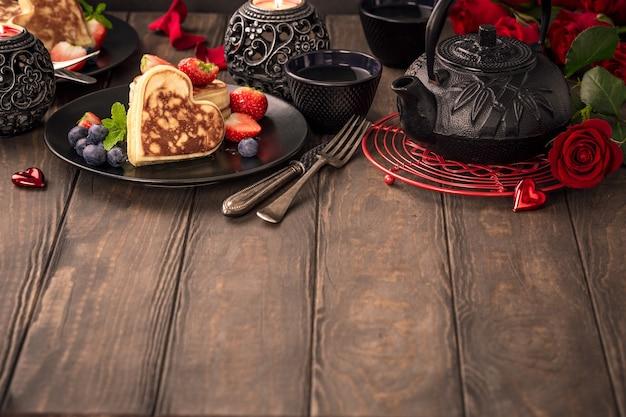 Surface de la saint-valentin avec de délicieuses crêpes en forme de cœur, thé vert, théière noire, bougies et roses. carte de voeux de concept de saint valentin. copier l'espace