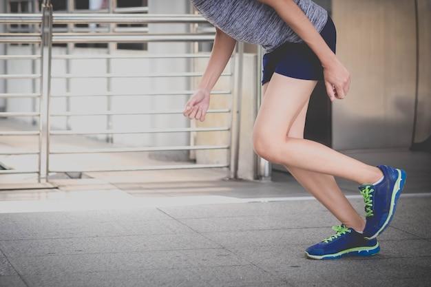 Surface sportive, gros plan des jambes d'un coureur urbain courir dans la rue avec espace de copie