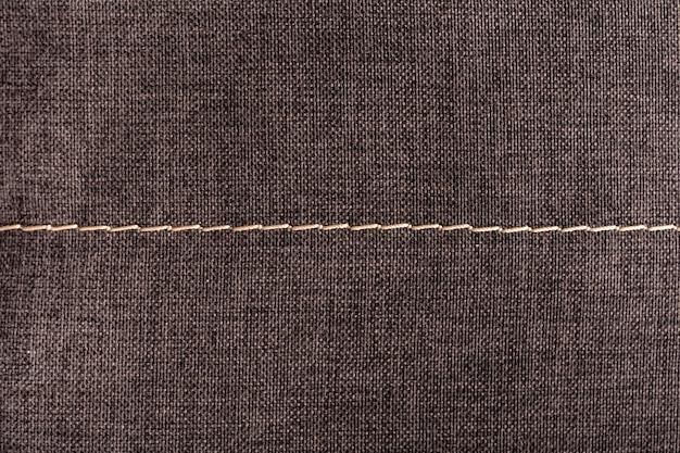 Surface textile avec coutures. fond gris texturé.