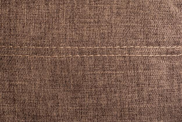 Surface textile avec coutures. fond marron texturé.