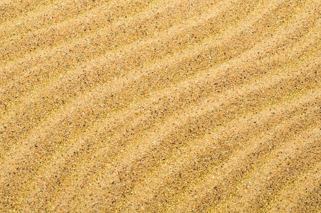 Surface de texture de sable de plage de mer avec des étincelles dorées