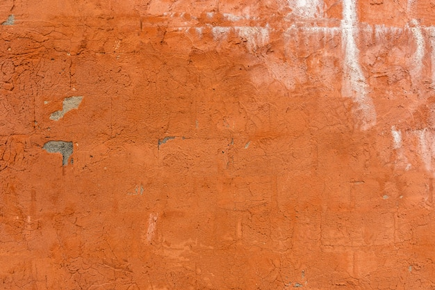 Surface texturée d'un vieux mur de béton peint en orange
