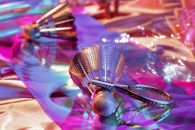Surface de tissus irisés arc-en-ciel holographique et objets du volant des années 90, raquette, cassette audio, rétrospective des années 80, concept sportif.