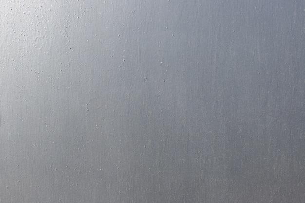 Surface d'une tôle peinte en peinture grise. fond argenté, texture métallique abstraite.