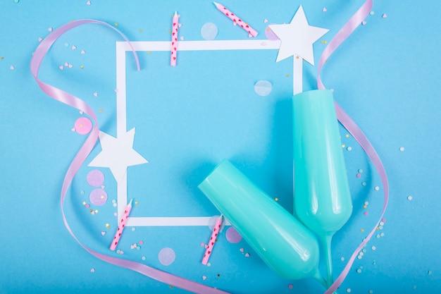 Surface de vacances de fête avec ruban, étoiles, bougies d'anniversaire, cadre vide de boîte-cadeau et confettis sur la surface bleue