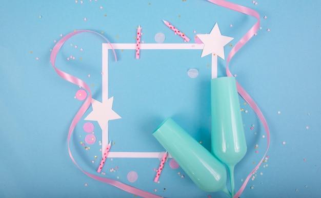 Surface de vacances de fête avec ruban, étoiles, bougies d'anniversaire, cadre vide et confettis sur surface bleue